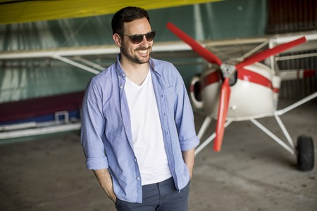 Handsome young man in the airplane hangar Stock Photo
