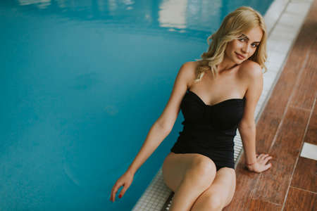 Pretty young woman relaing by the indoor swimming pool Standard-Bild