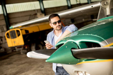 Handsome young pilot checking his ultralight airplane in the hangar before flight