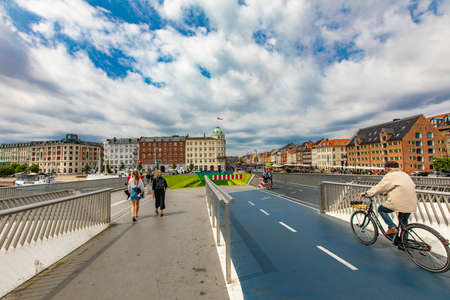 COPENHAGEN, DENMARK - JUNE 14, 2018: Unidentified people on Inderhavnsbroen bridge in Copenhagen, Denmark. It is combined pedestrian and bicyclist bridge opened at 2016. Editöryel