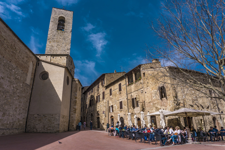 SAN GIMIGNANO, ITALY - APRIL 8, 2018: Unidentified people on the street of San Gimignano, Italy. Historic Centre of San Gimignano is designated as    Site since 1990.