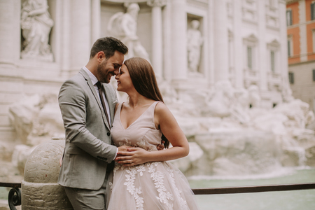 Just married bride and groom posing in front of Trevi Fountain (Fontana di Trevi), Rome, Italy Stockfoto