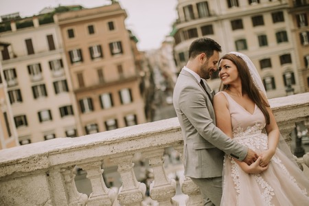 Young attractive newly married couple  posing in Rome with beautiful and ancient architecture in the background