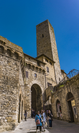 SAN GIMIGNANO, ITALY - APRIL 8, 2018: Unidentified people on the street of San Gimignano, Italy. Historic Centre of San Gimignano is designated as UNESCO World Heritage Site since 1990.