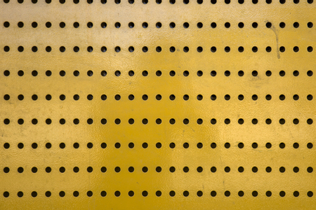 Background of yellow metal texture with holes
