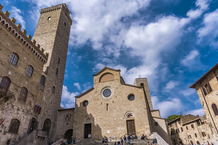 SAN GIMIGNANO, ITALY - APRIL 8, 2018: Unidentified people on Piazza del Duomo at San Gimignano, Italy. Historic Centre of San Gimignano is designated as    Site since 1990.