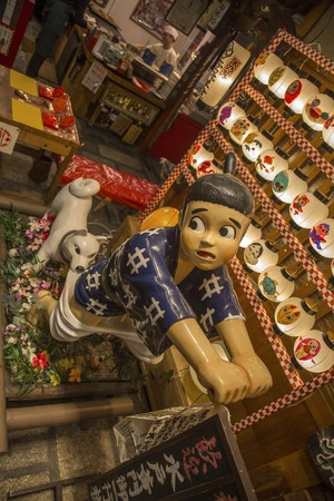 KYOTO, OCTOBER 8, 2016: Detail from okonomiyaki restaurant Issen Yoshoku in Kyoto, Japan. This Japanese savory pancake restaurant is famous for its sign, dog chasing a boy thief