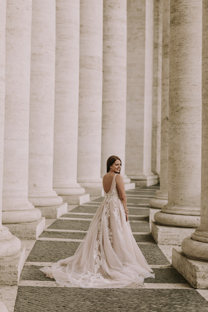 Pretty young bride in wedding dress in the Vatican colonnade Stock Photo