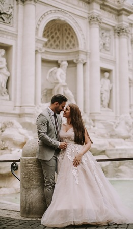 Just married bride and groom posing in front of Trevi Fountain (Fontana di Trevi), Rome, Italy Stock Photo