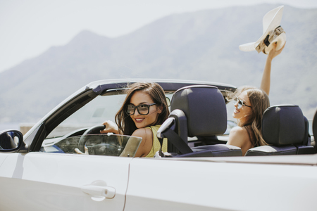 Young women with sunglasses driving her convertible top automobile on bright sunny day near sea