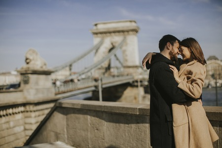 Young happy attractive couple in love hugging with background of the magnificent view of Budapest, Hungary Banco de Imagens