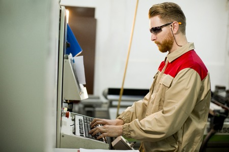 Handsome young man working at machine in the factory