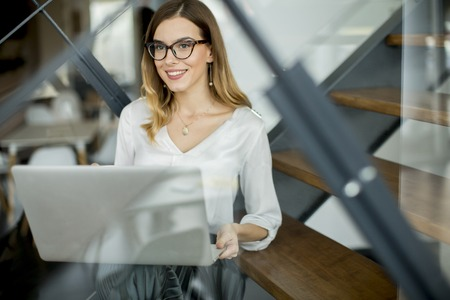 Pretty young woman working at laptop in the office