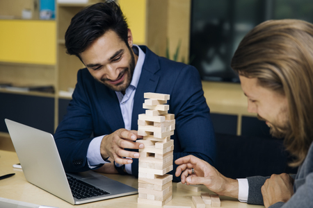 Team of young business people build a wooden construction in the office Stock Photo