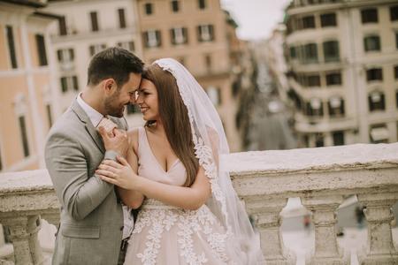 Jong aantrekkelijk pas getrouwd stel poseren in Rome met mooie en oude architectuur op de achtergrond