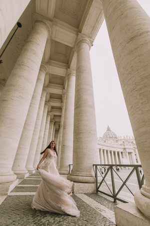Pretty young bride in wedding dress in the Vatican colonnade 스톡 콘텐츠