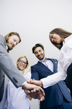 Closeup of young coworkers putting hands together as symbol of unity in the office Stockfoto