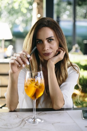 Portrait of attractive young woman drinking coctail in cafe outdoor