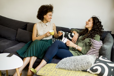Two multiracial young women chatting and drinking coffe in rhe living room