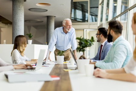 Senior boss holds a meeting for younger colleagues in the modern office