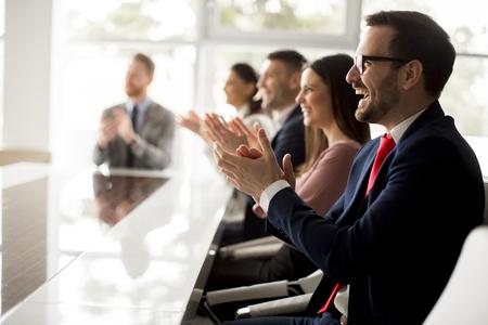 Biznesmeni biją brawo podczas spotkania w nowoczesnym biurze Zdjęcie Seryjne