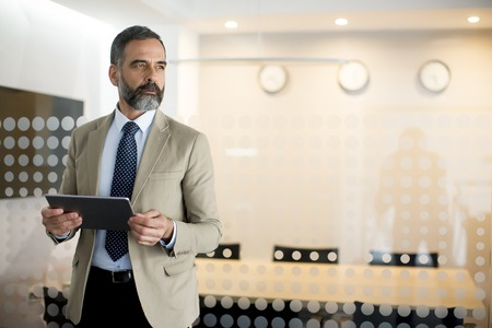 Portrait of senior businessman with digital tablet standing in office