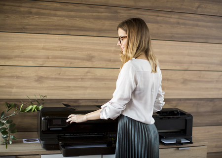 Young business woman working in office by the printer Stock Photo