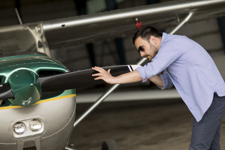 Handsome young pilot checking ultralight airplane before flight Stock Photo