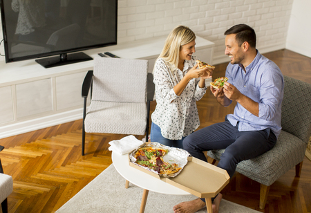 Loving couple relaxing at home and eating tasteful pizza