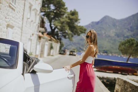 Pretty young woman with sunglasses by the white cabriolet car