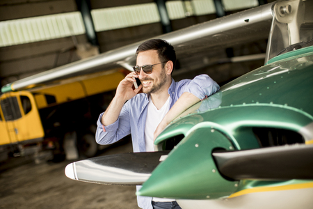 A young handsome pilot checking the airplane in the hangar and using mobile phone 版權商用圖片
