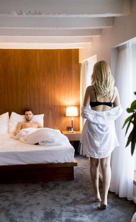 De jonge man wacht thuis op een vrouw in bed