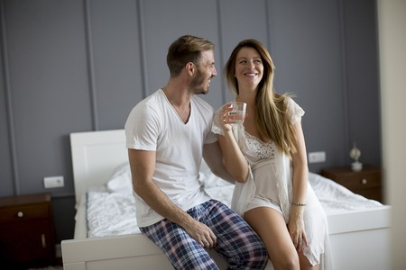 Young couple posing in the bedroom, woman holding glass of water