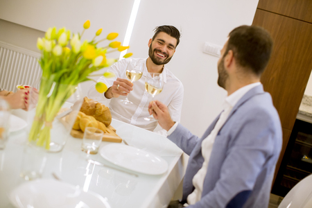 Two young men have dinner and toasting white wine