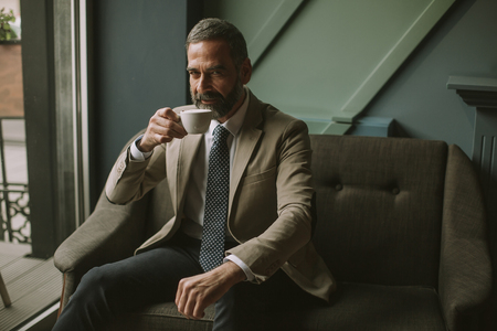 Handsome elegant serious businessman sitting in armchair and holding cup of espresso in cafe