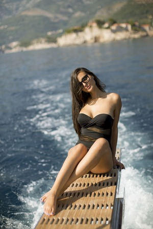 Pretty young woman relaxing on the yacht at sea on a sunny summer day