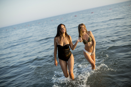Two pretty young women having fun on the beach by the sea at sunset