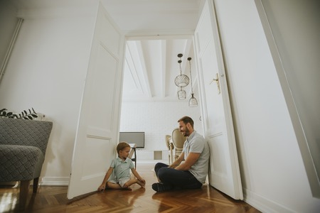 Happy father with his son playing at home on the floor