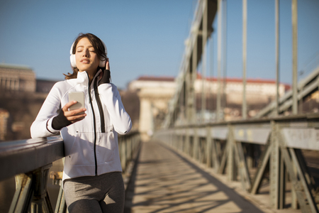 Young athlete woman with mobile phone on the bridhe in Budapest, Hungary Stock Photo