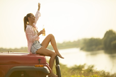 Young woman sits on a car hood,  drinks refreshment and enjoys it Reklamní fotografie