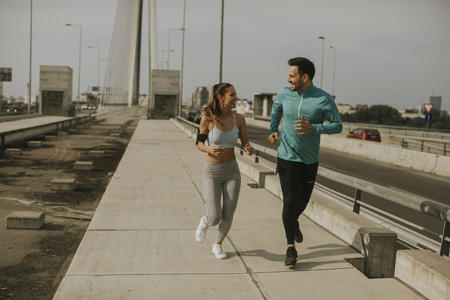 Young couple running in urban enviroment at sunny day