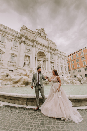 Lovely young wedding couple by Trevi fountain in Rome, Italy Stock Photo