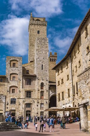 SAN GIMIGNANO, ITALY - APRIL 8, 2018: Unidentified people at Piazza della Cisterna in San Gimignano, Italy. Historic Centre of San Gimignano is designated as UNESCO World Heritage Site since 1990. Редакционное