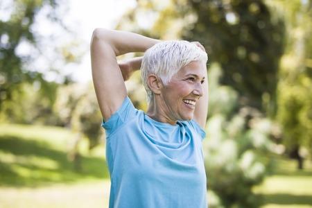 Porträt der älteren Frau, die Übung für das Strecken der Arme im Park tut Standard-Bild