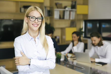 Portrait of young businesswoman standing in the office and other young business people working in the background
