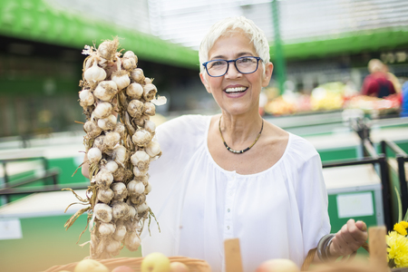 Portrait of senior woman buying lot of garlic on market