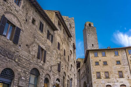 SAN GIMIGNANO, ITALY - APRIL 8, 2018: Old street of San Gimignano, Italy. Historic Centre of San Gimignano is designated as UNESCO World Heritage Site since 1990.