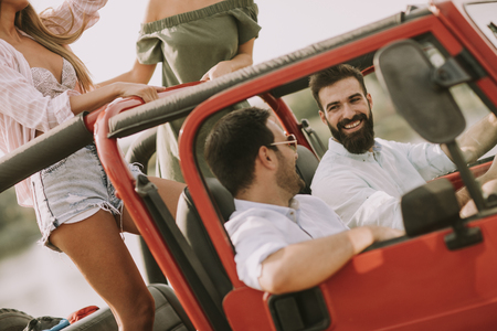 Happy friends having fun in convertible car at vacation by river Stockfoto
