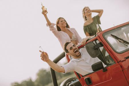 Happy friends having fun in convertible car at vacation by river Archivio Fotografico