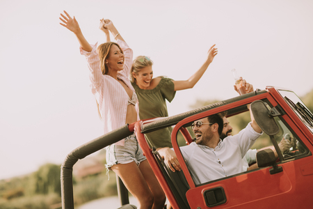 Happy friends having fun in convertible car at vacation by river Stockfoto - 107905322